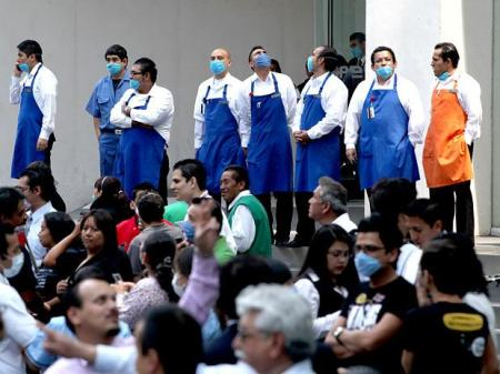 No México, trabalhadores usam máscaras para evitar a contaminação